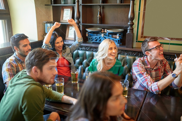 friends with beer watching football at bar or pub Stock photo © dolgachov