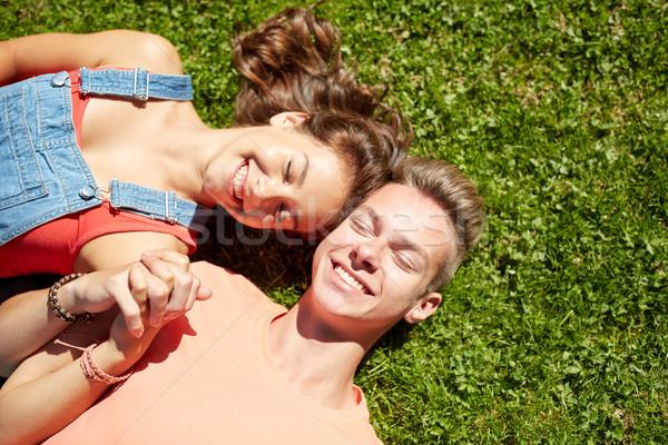 happy teenage couple lying on grass at summer Stock photo © dolgachov