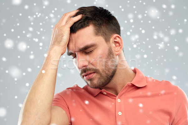 unhappy man suffering from head ache over snow Stock photo © dolgachov