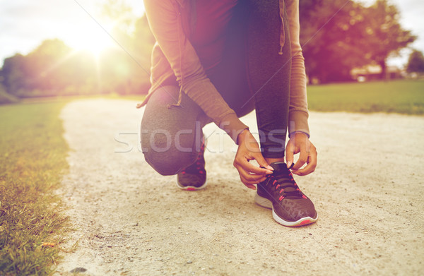 close up of woman tying shoelaces outdoors Stock photo © dolgachov