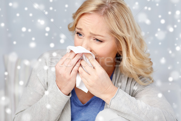ill woman blowing nose to paper napkin Stock photo © dolgachov