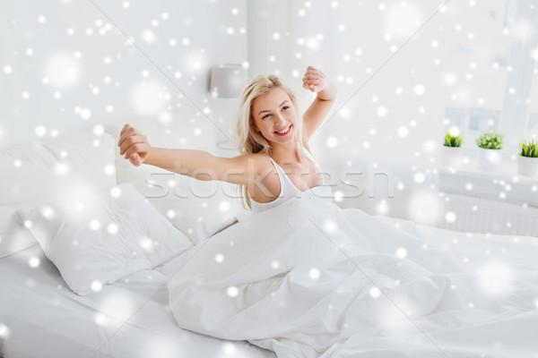 Fiatal nő nyújtás ágy otthon hálószoba alszik Stock fotó © dolgachov