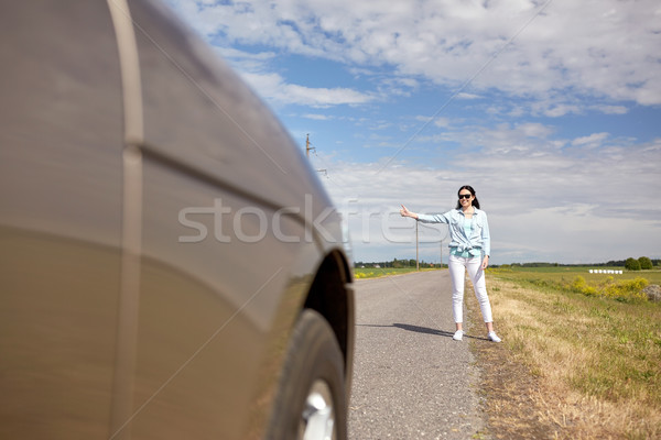 woman hitchhiking and stopping car with thumbs up Stock photo © dolgachov