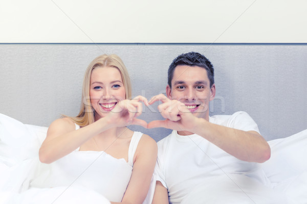 smiling couple showing heart with hands Stock photo © dolgachov