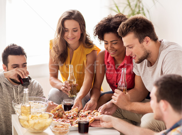 happy friends with drinks eating pizza at home Stock photo © dolgachov
