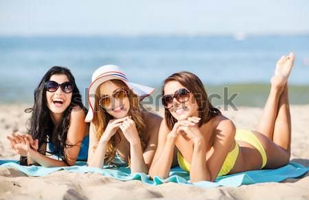 Grupo sorridente mulheres alimentação sorvete praia Foto stock © dolgachov