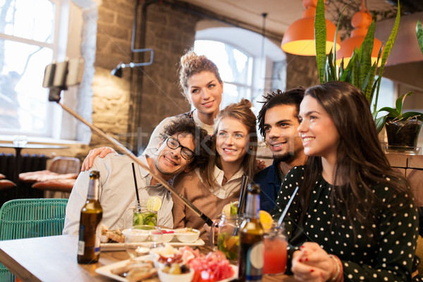 friends taking selfie by smartphone at bar or cafe Stock photo © dolgachov