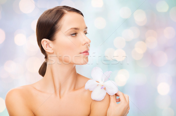 beautiful young woman with orchid flower Stock photo © dolgachov