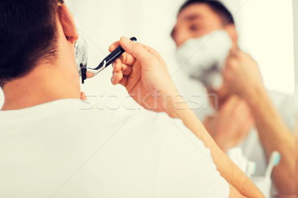 close up of man shaving beard with razor blade Stock photo © dolgachov