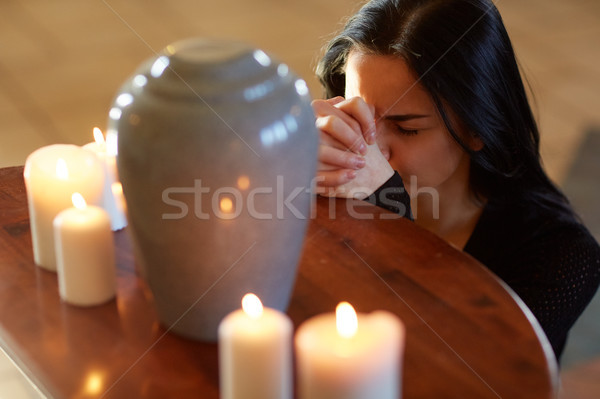 Stock photo: sad woman with funerary urn praying at church