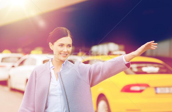 Glimlachend jonge vrouw hand taxi reizen Stockfoto © dolgachov