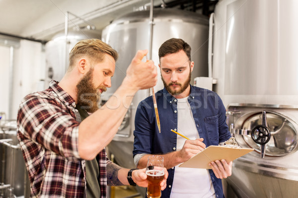 men with pipette testing craft beer at brewery Stock photo © dolgachov