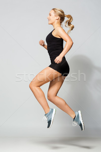 young woman in black sportswear jumping Stock photo © dolgachov