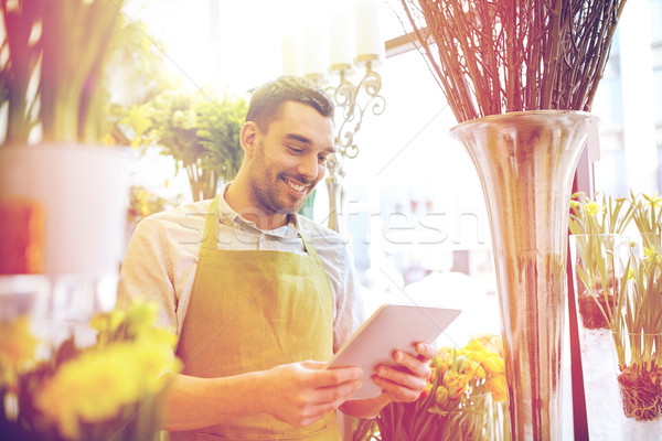 man with tablet pc computer at flower shop Stock photo © dolgachov