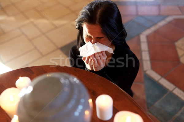 Stock photo: woman with cremation urn crying in church