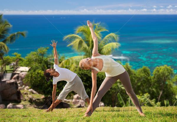 happy couple doing yoga outdoors Stock photo © dolgachov