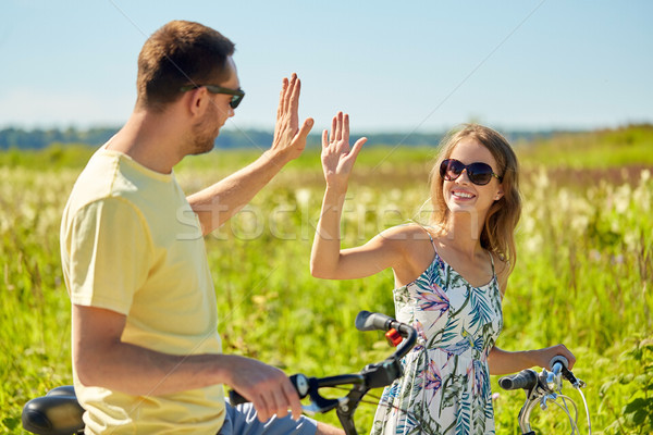 happy couple with bicycles making high five Stock photo © dolgachov