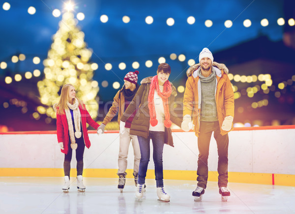 Stock photo: happy friends on christmas skating rink