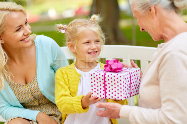 Stock photo: happy family giving present to grandmother at park