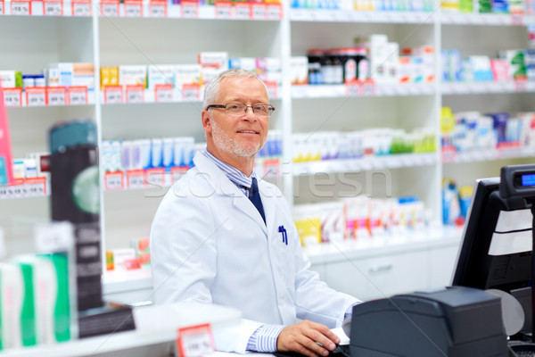 senior apothecary at pharmacy cash register Stock photo © dolgachov