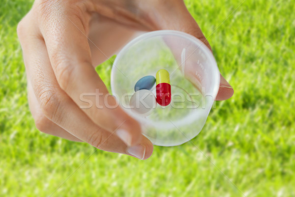 Stock photo: close up of female hand with pills in medicine cup
