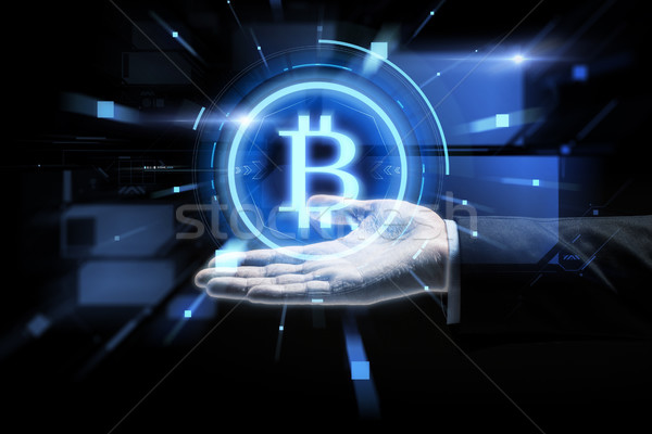 Stock photo: close up of businessman hand with bitcoin symbol