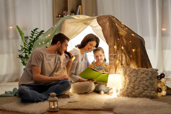 happy family reading book in kids tent at home Stock photo © dolgachov