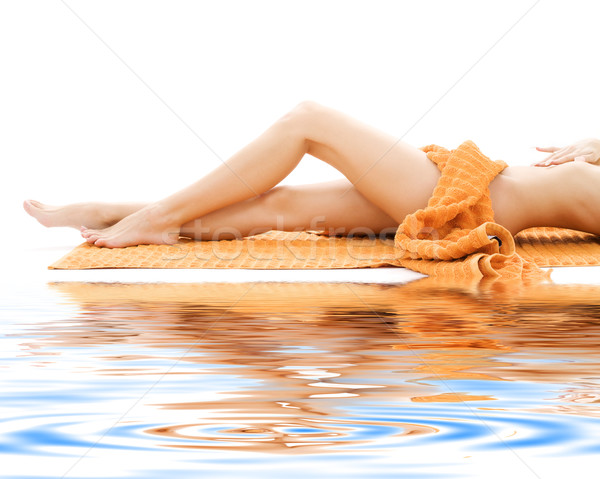 long legs of relaxed lady with orange towel Stock photo © dolgachov
