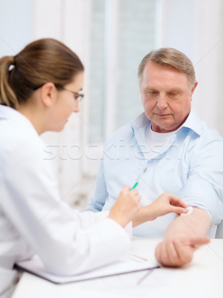 female doctor doing injection to old man Stock photo © dolgachov