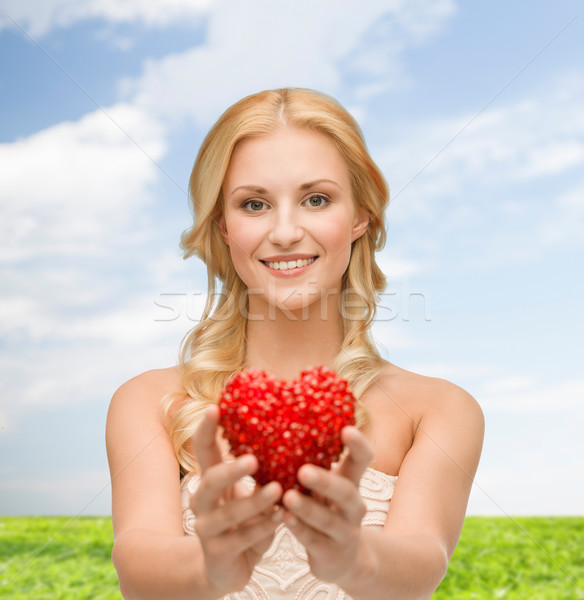 smiling woman giving small red heart Stock photo © dolgachov
