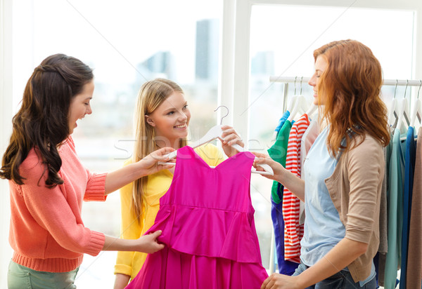 three smiling friends trying on some clothes Stock photo © dolgachov