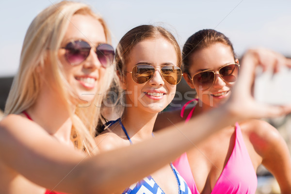 Stock photo: group of smiling women making selfie on beach