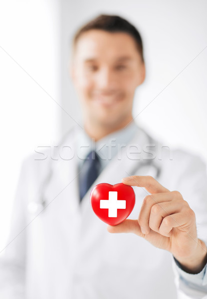 male doctor holding heart with red cross symbol Stock photo © dolgachov
