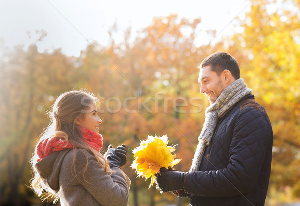 smiling couple with bunch of leaves in autumn park Stock photo © dolgachov
