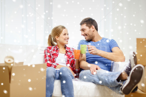 Stock photo: smiling couple drinking tea or coffee at new home