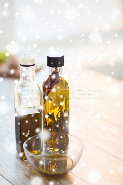 Stock photo: close up of two olive oil bottles and glass bowl