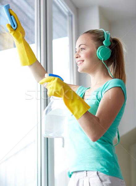 happy woman with headphones cleaning window Stock photo © dolgachov