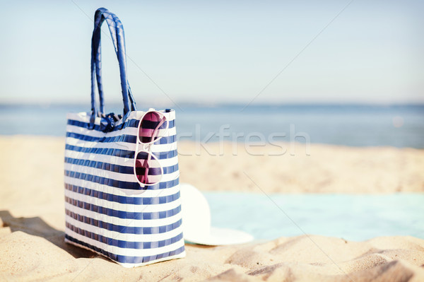 straw hat, sunglasses and bag lying in the sand Stock photo © dolgachov