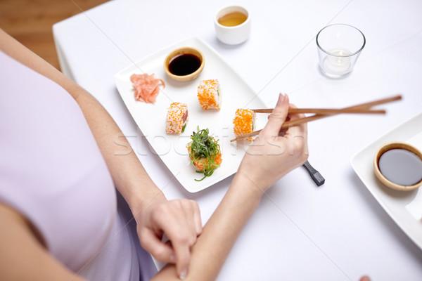 close up of woman eating sushi at restaurant Stock photo © dolgachov