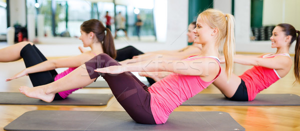 group of smiling women exercising in the gym Stock photo © dolgachov
