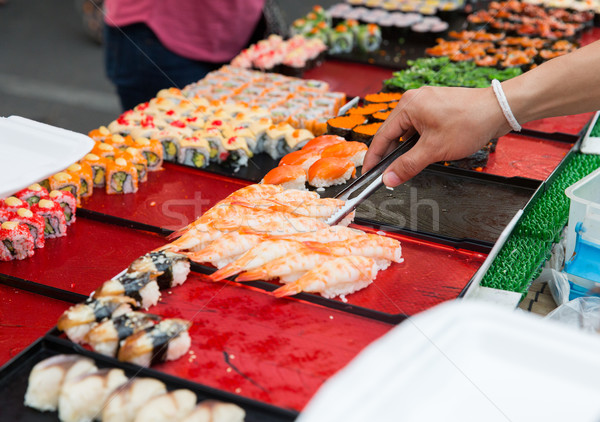 close up of hand with tongs taking sushi Stock photo © dolgachov