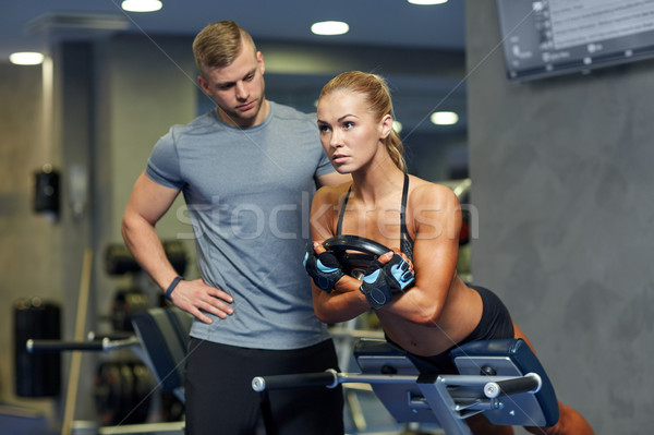 woman with personal trainer flexing muscles in gym Stock photo © dolgachov