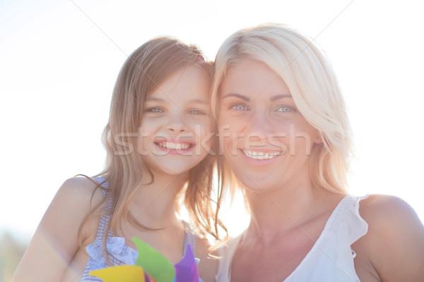 happy mother and child girl with pinwheel toy Stock photo © dolgachov