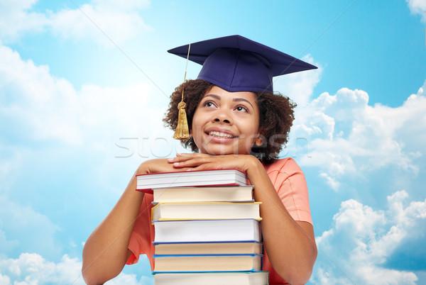 Gelukkig afrikaanse vrijgezel meisje boeken hemel Stockfoto © dolgachov