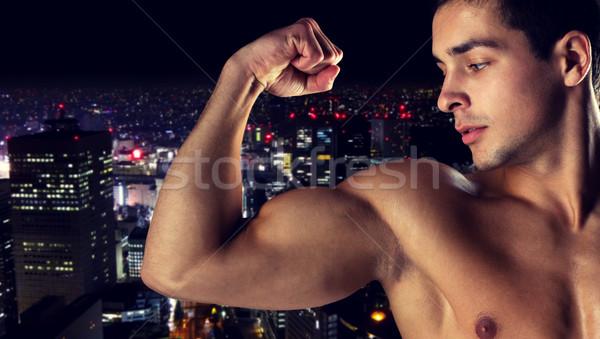 Jonge man tonen biceps sport bodybuilding Stockfoto © dolgachov