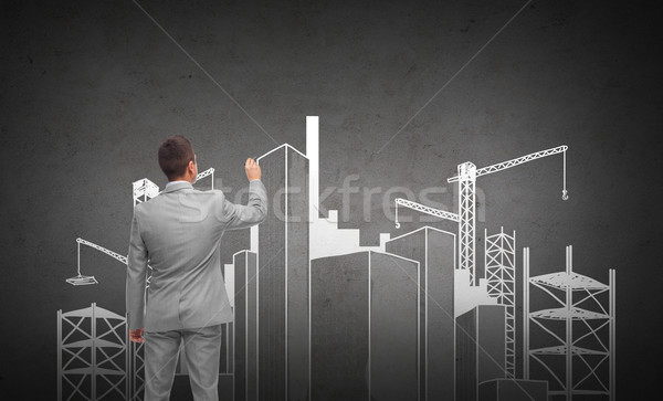 businessman drawing city construction site Stock photo © dolgachov