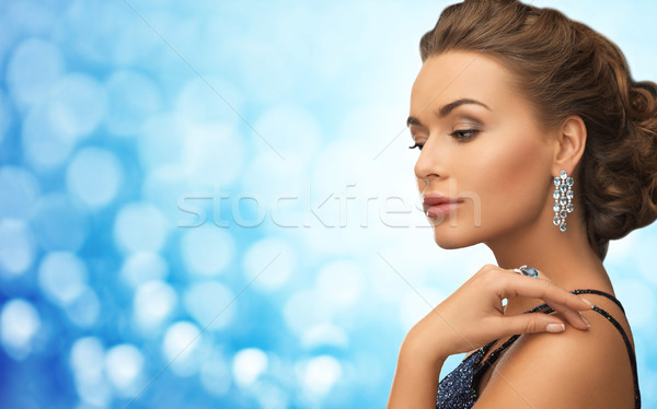 woman with beautiful diamond earrings over blue Stock photo © dolgachov