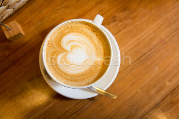 Stock photo: close up of coffee cup with heart shape drawing