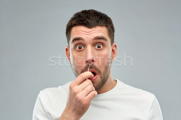 man with tweezers tweezing hair from nose Stock photo © dolgachov