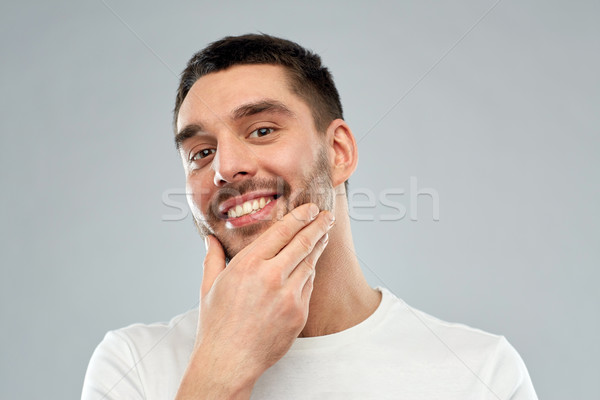 happy young man touching his face or beard Stock photo © dolgachov